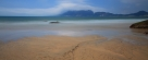 正午,蓝天白云与沙滩相伴。