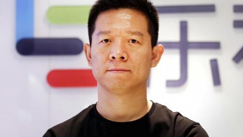 Jia Yueting, LeEco founder, poses for a photo in front of a logo of his company in Beijing.