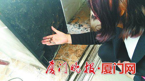 小张蹲下来查看冰箱烧损的情况。