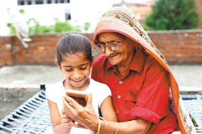 58%的印度农村用户通过互联网观看线上视频,而其中65%—75%是通过手机的4G网络观看。图为在印度的一个村庄,奶奶和孙女一起用智能手机观看视频。 人民视觉