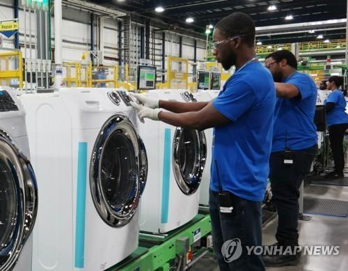 三星电子美国工厂内,一名美国工人正在检查洗衣机(图片来自韩联社网站)