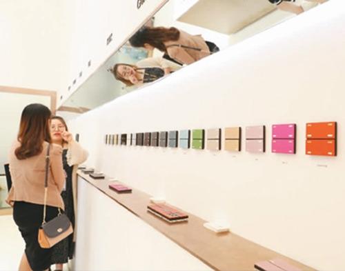 在某国际智能家居展览会上,工作人员向参观者介绍彩色智能开关面板。